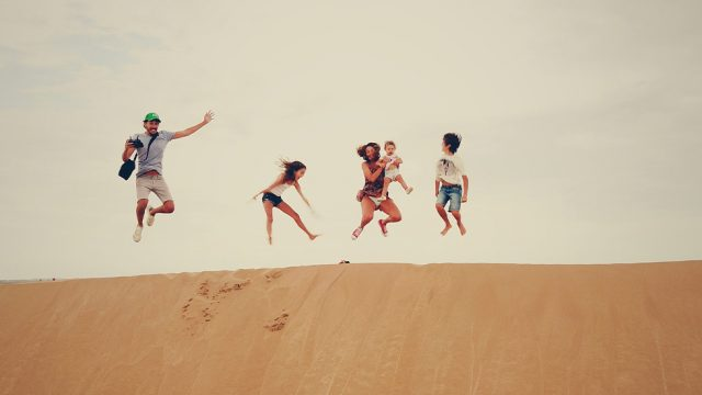 Familie springt auf Sanddüne